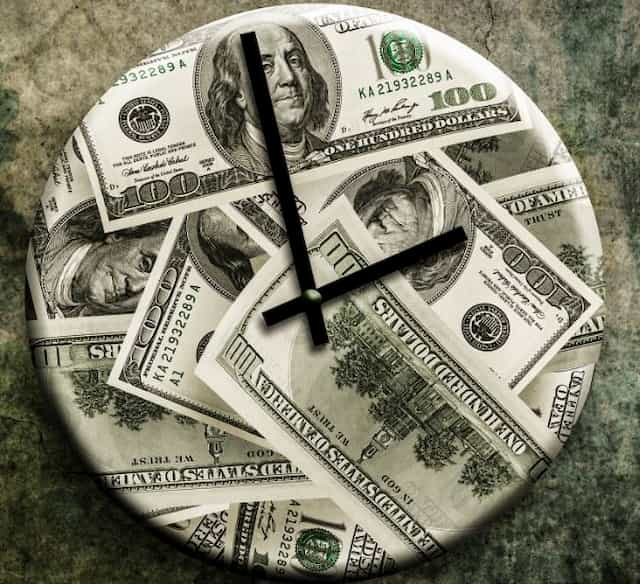 Clock with a background of dollar bills