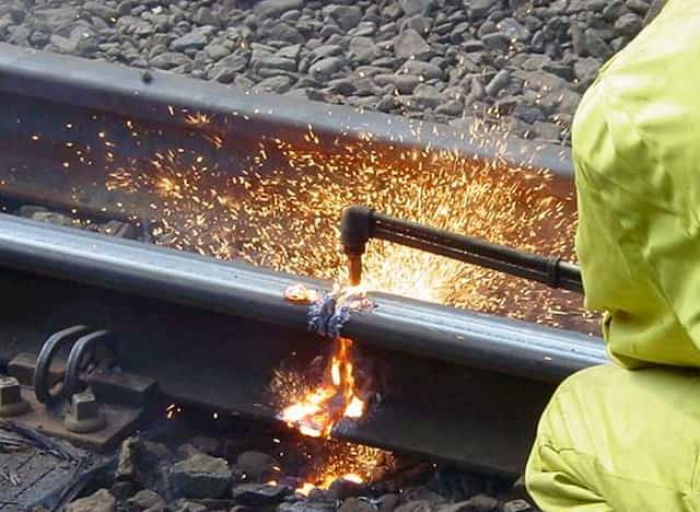 Man cutting a rail with a oxyfuel torch